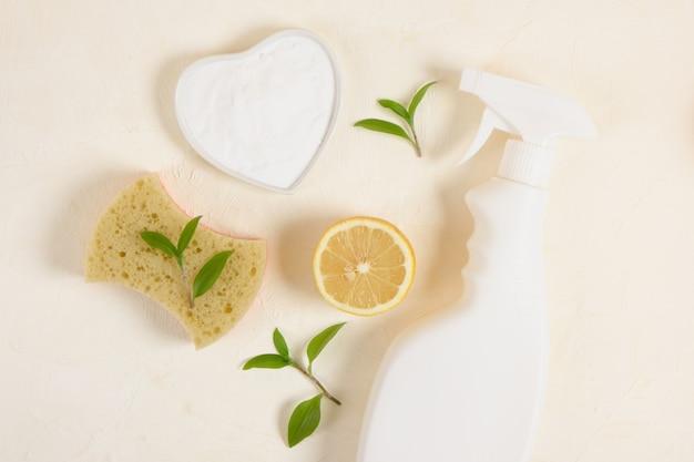 ベーキングソーダを使って、ベージュのバックグラウンドトップバイアコピースペースソーサーにボトル、スポンジ、レモン、ソーダをスプレーします。環境にやさしいコンセプトを洗浄するための無毒洗剤
