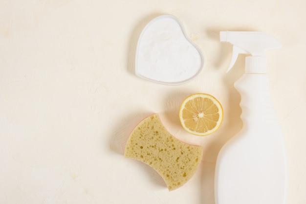 ベーキングソーダを使って、ベージュのバックグラウンドトップバイアコピースペースソーサーにボトル、スポンジ、レモン、ソーダをスプレーします。洗浄用の無毒洗剤