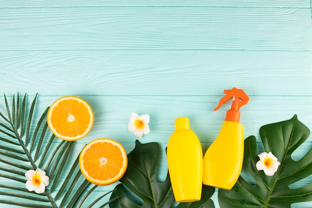 Spray bottles with fruits and plant leaves