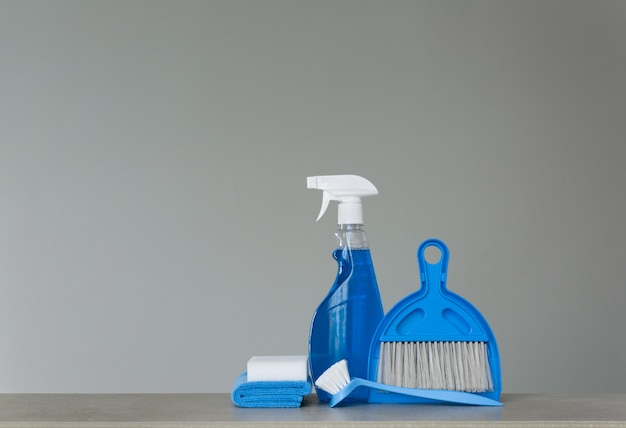Spray detergent, dishwashing brush, dust cloths, sponge, scoop and broom. copy space.