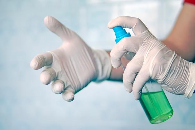 Распылительная дезинфицирующая жидкость, рука в белой перчатке на синем фоне, дезинфекция в домашних условиях. убивает микробы, бактерии. антибактериальное, противовирусное средство в форме спрея. антибактериальная жидкость против covid 19.