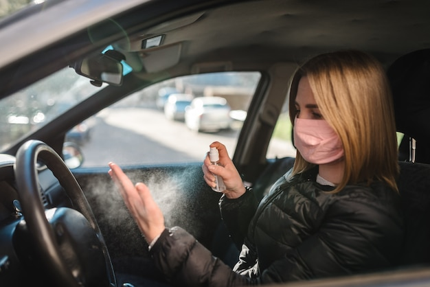 Spraying antibacterial sanitizer spray on hand in car, infection control concept. sanitizer to prevent coronavirus, covid-19, flu. spray bottle. woman wearing in medical protective mask driving a car.