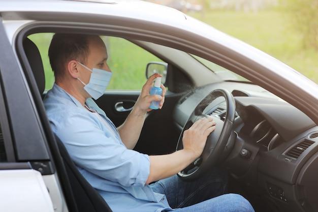 ハンドル車、感染制御の概念に抗菌消毒スプレーを噴霧します。コロナウイルス、covid-19、インフルエンザを予防します。車を運転して医療用防護マスクを着た男。ワイプの消毒。