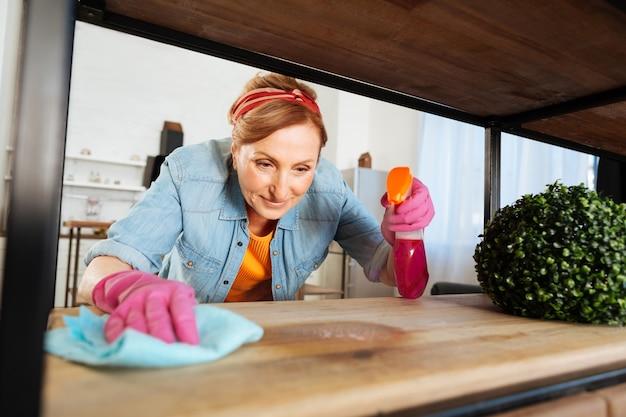 스프레이 청소 제품. 그녀의 집을 주문하는 동안 나무 선반에 청소 스프레이를 적용하는 쾌활한 근면 한 아가씨