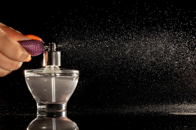 Spraying perfume bottle glass on a black background.