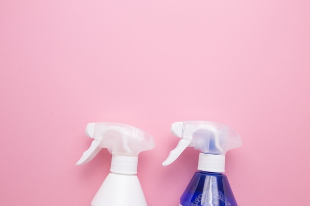 Sprays for cleaning on a pink background close-up.