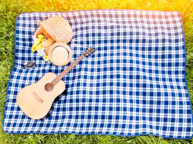 Spread checkered plaid with picnic basket and guitar on meadow