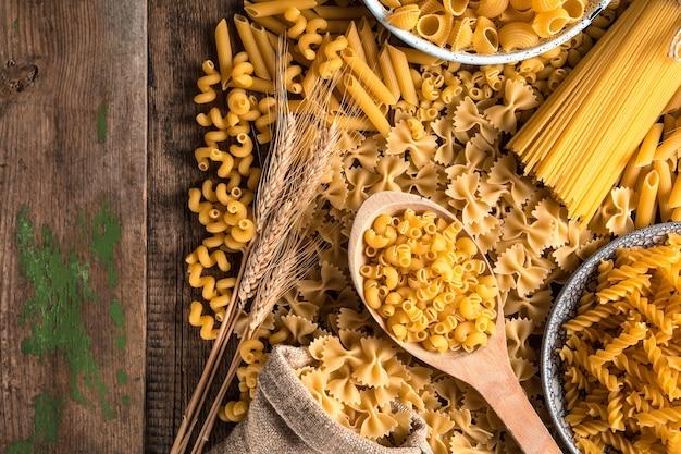 Разложите на деревянном столе макароны разных сортов.