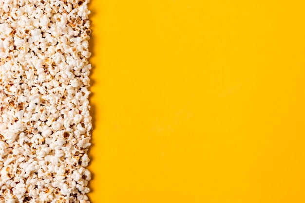 Spread popcorns on yellow background