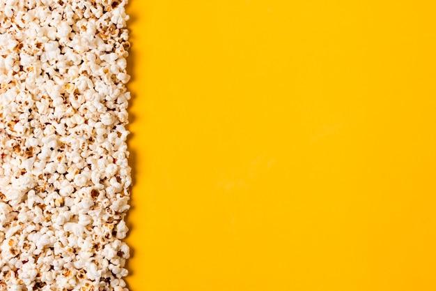 Spread popcorns on yellow background
