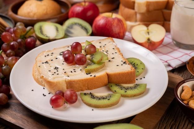 Намажьте хлеб джемом и выложите его с киви и виноградом на белую тарелку.
