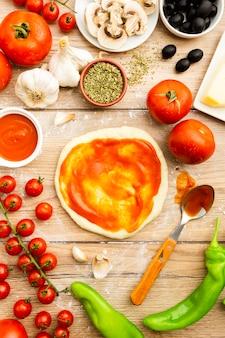 Spread tomato sauce on pizza dough