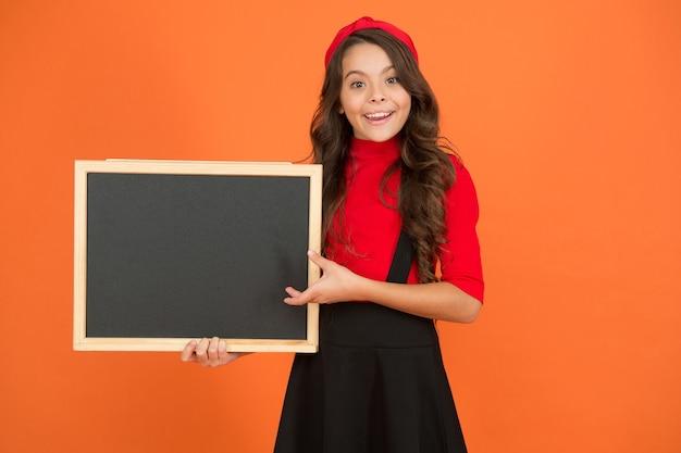 あなたの宣伝を広めなさい。幸せな子供は学校の宣伝のために空白の黒板を持っています。小さな子供はきちんとした宣伝板で微笑む。広告とマーケティング。広報機関、コピースペース。