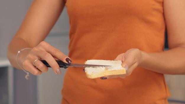 맛있는 아침 식사를 위해 구운 빵에 버터를 바르십시오. 빵 조각에 부드러운 버터를 바르는 칼. 건강한 생활 방식, 아늑한 주방에서 아침 맛있는 식사를 만드세요. 전통적인 맛있는 점심