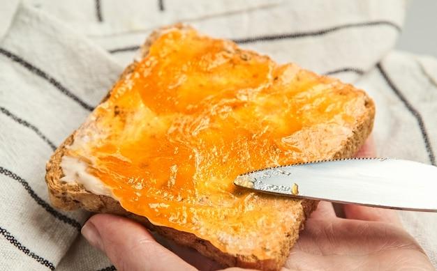 スライスされたパンにジャムを広げます。ビーガンバターと自家製フルーティージャムで乾杯。