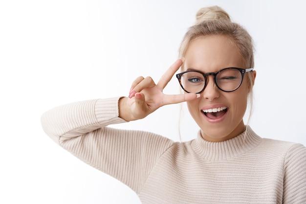 Распространение позитива. крытый снимок красивой кавказской белокурой женщины в очках и свитере, подмигивающей нахально улыбающейся, демонстрирующей победу или жест мира над дискотекой, танцующей от радости и счастья