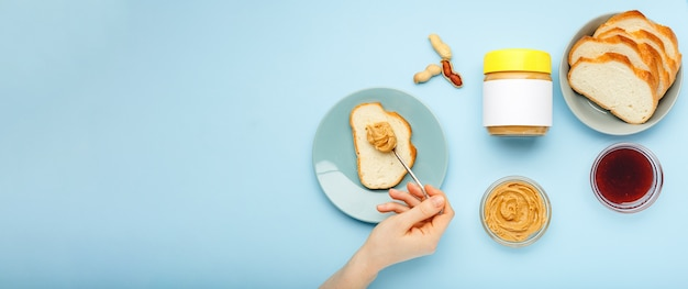 Spreading toast with peanut butter, peanut paste by female hands on blue background. cooking process