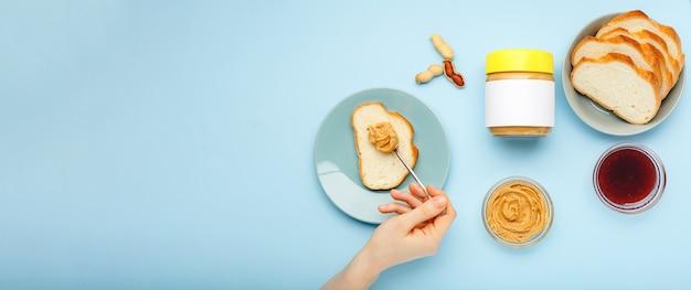 ピーナッツバター、青い背景の上の女性の手によるピーナッツペーストでトーストを広げます。調理プロセス