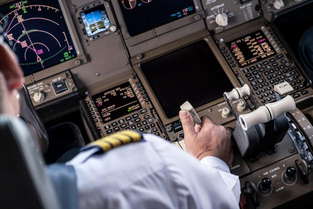 Капитан авиалайнера управляет самолетом в кабине, вытягивая рычаг тормоза spreed для замедления скорости самолета.