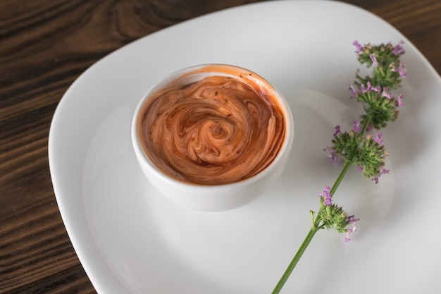 Sprig of herbs and sauce in a white bowl on a wooden table. vegetarian sauce. sauce for meat and fish.