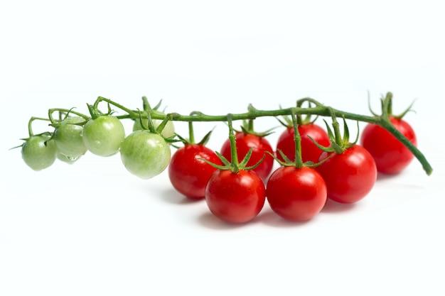 Веточка помидоров черри на белой поверхности