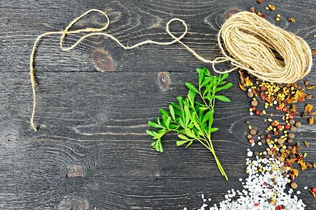 塩、コショウ、フェヌグリークの種子と黒い木の板に対するより糸のコイルと新鮮な緑のrueの小枝