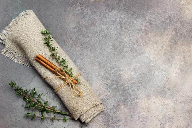 Веточка тимьяна и палочка корицы на льняной салфетке.