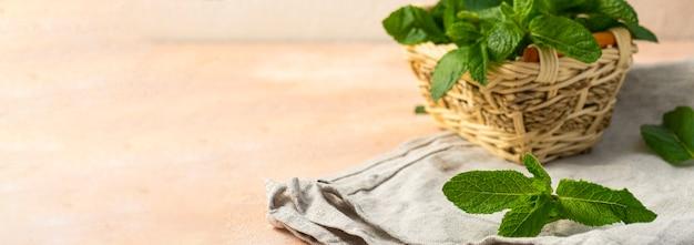 Sprigs of green fresh mint in a wicker basket on wooden table
