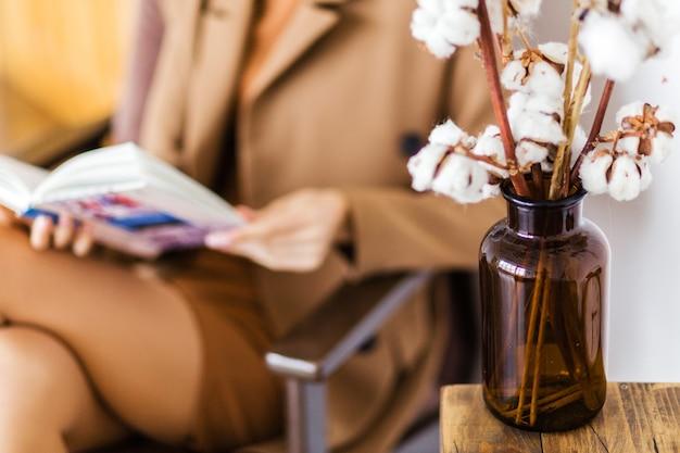 綿の小枝が瓶の形をしたガラスの花瓶の中に立っており、背景には女の子が肘掛け椅子に座って本を読んでいます。写真