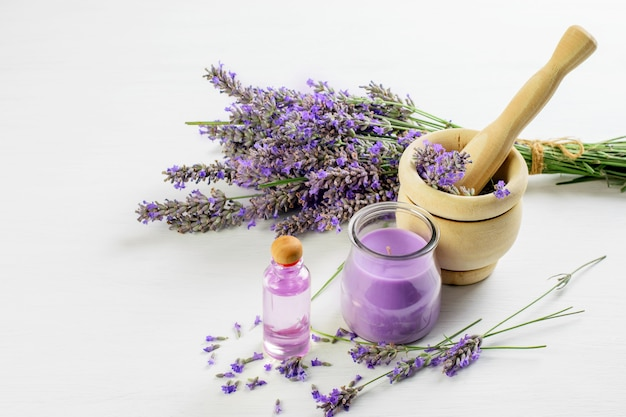 ラベンダーの小枝、乳鉢のラベンダーの花、ラベンダーの皮のオイル、キャンドル。スキンケア、アロマセラピーのコンセプトです。