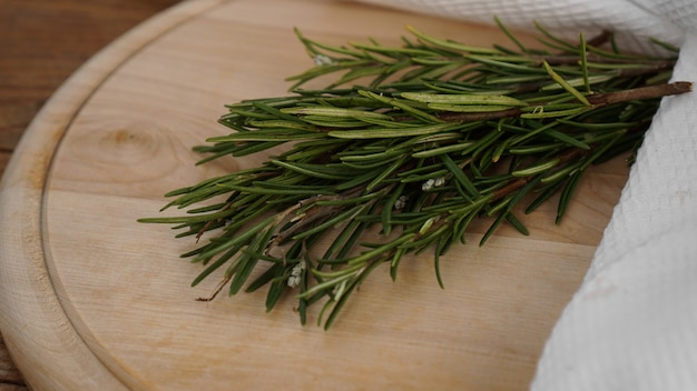 切断用の木の板にローズマリーの小枝。素朴なスタイル。スパイス