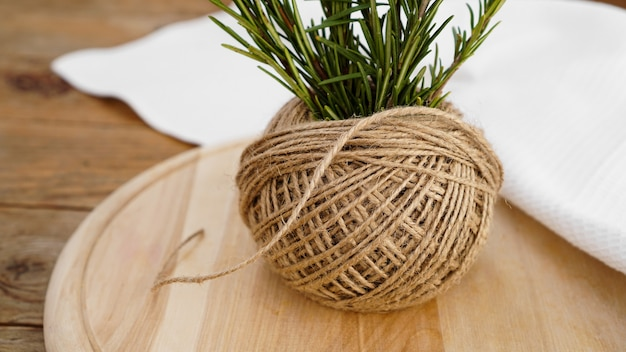 Sprigs of rosemary and skeins of jute rope on a wooden board for cutting. rustic style. spice
