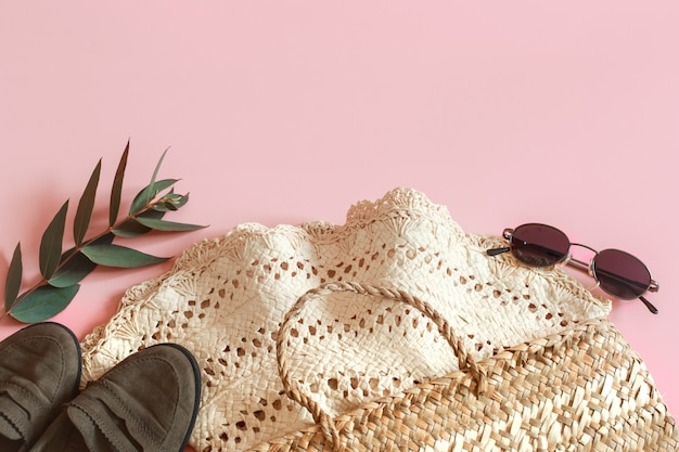 ピンクの背景の春のアクセサリーと服