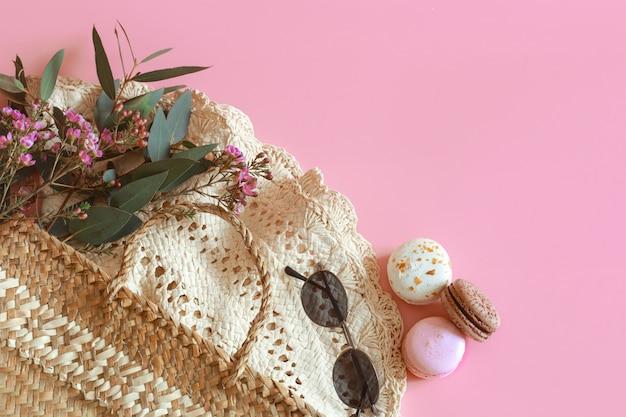 ピンクのテーブルの上の春のアクセサリーと服