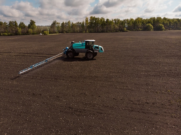 Spring agricultural work in the fields. the tractor sprays crops with herbicides, insecticides and pesticides.