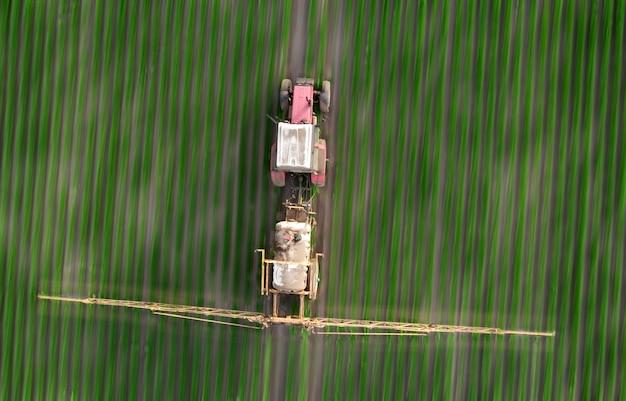 들판에서 봄 농업 작업. 트랙터는 농작물에 제초제, 살충제 및 살충제를 뿌립니다.