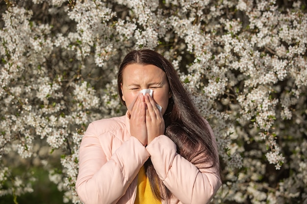 Spring allergy symptoms concept, young woman sneezing in front of blooming a tree, allergy to pollen and flowering season, healthcare