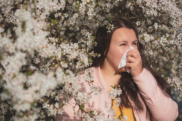 春のアレルギー症状のコンセプト、花が咲く木の前でくしゃみをする若い女性、花粉と開花期のアレルギー、医療