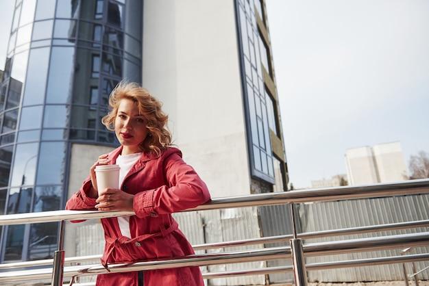 春とファッションのコンセプトです。暖かい赤いコートを着た大人のきれいな女性が彼女の週末の時間に街を歩いている