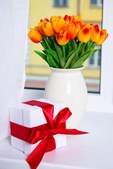 春と休日のコンセプト美しいオレンジ色の人工チューリップと窓枠のギフトボックス