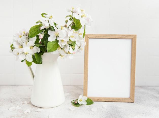 テーブルの上に空のフォト フレームが付いている花瓶の春のリンゴの花