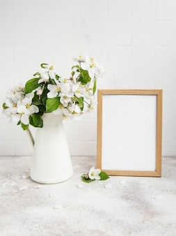 Spring apple blossom in a vase with an empty photo frame on the table
