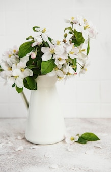 Spring apple blossom in a white vase on the table