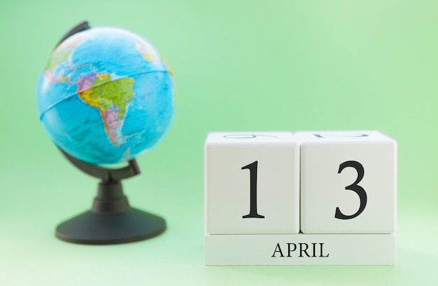 Spring april 13 calendar. part of a set on blurred green background and globe.