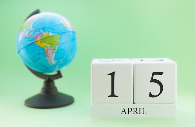 Spring april 15 calendar. part of a set on blurred green background and globe.