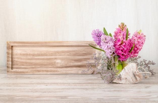 Spring arrangement with hyacinth flowers and wooden heart
