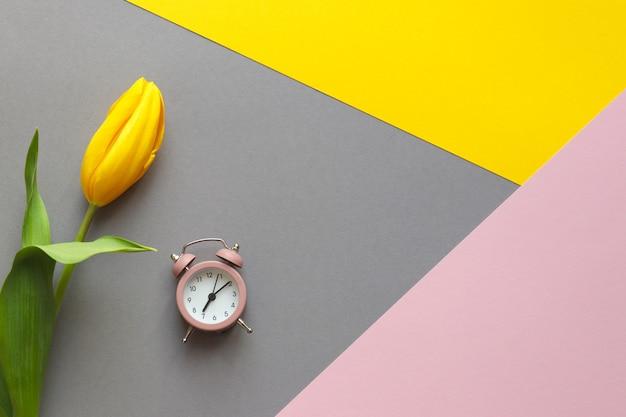 春の目覚めのコンセプト黄色のチューリップの花と幾何学的な黄色の灰色とピンクのテーブルの目覚まし時計