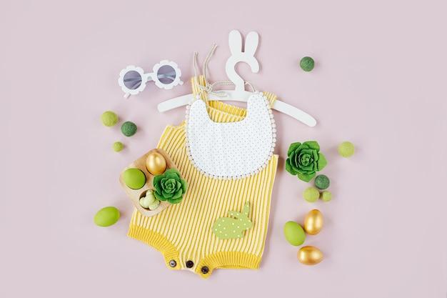 Весенняя детская одежда. вязаное боди на милой вешалке с кроличьими ушками с пасхальными украшениями и яйцами на бледно-розовом фоне. концепция праздника. плоская планировка, вид сверху