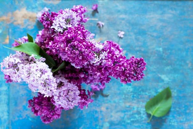春の背景。青い木製の背景に美しい新鮮なライラックバイオレットの花。上面図。