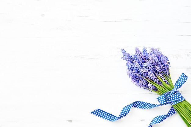 Spring background. blue muscari flowers bouquet decorated with ribbon on white wooden background. copy space, top view